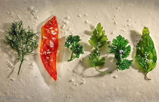 Friske krydderurter og rød peber på række med flagesalt drysset over.