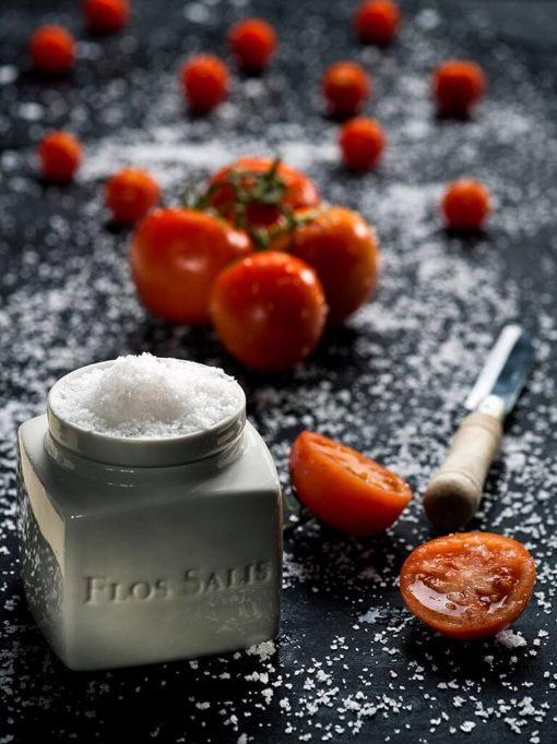Flos Salis med Flor de Sal på låget og friske udskårede tomater på sort bordplade